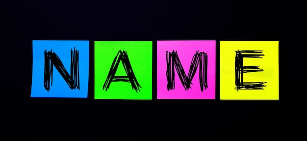 Em uma superfície preta, adesivos multicoloridos brilhantes com a palavra nome