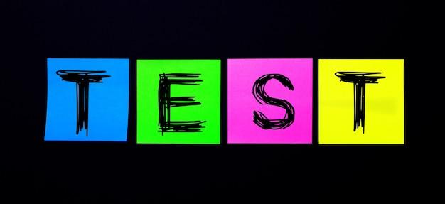 Em uma superfície preta, adesivos multicoloridos brilhantes com a palavra teste
