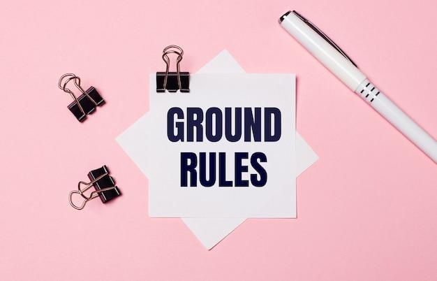 Em uma superfície rosa claro, clipes de papel pretos, uma caneta branca e um papel branco com o texto regras fundamentais