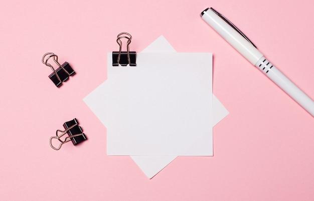 Em uma superfície rosa claro, clipes de papel pretos, uma caneta branca e um papel branco