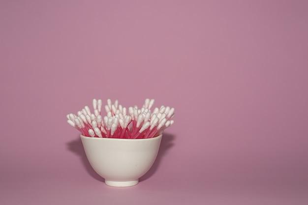Em uma superfície rosa, há cotonetes rosa em um copo branco.