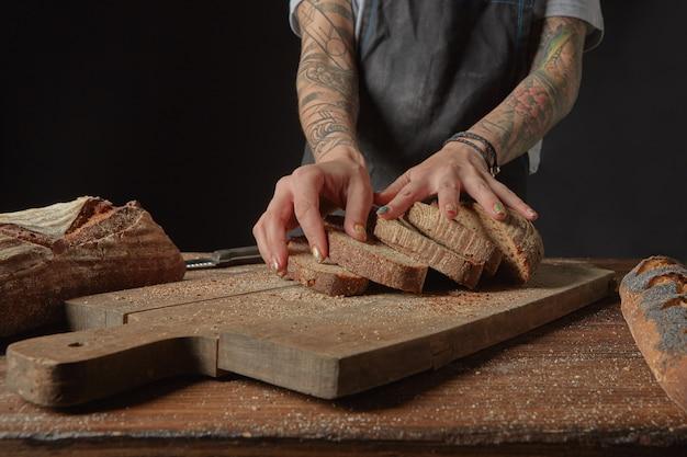 Em uma tábua de corte de madeira, uma mulher com tatuagens nas mãos segurando pedaços de pão fresco