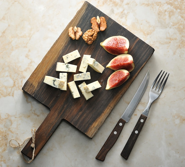 Em uma tábua de madeira, queijo com mofo azul dorblu, alguns figos e nozes.