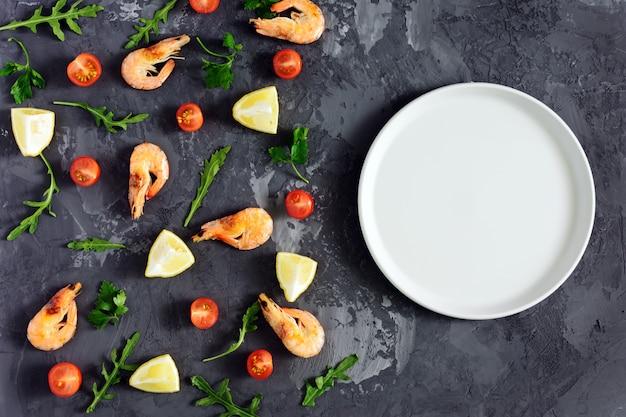 Em uma textura escura, há um prato cinza vazio, camarão, limão e verduras.