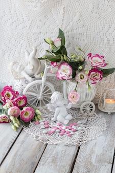 Em uma toalha de mesa de renda branca flores cor de rosa em um vaso, castiçal de anjos branco com uma vela