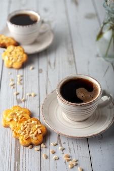 Em uma velha mesa de madeira branca, uma xícara de café aromático.
