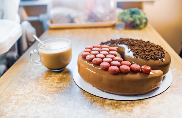 Em uma velha mesa de madeira há um lindo bolo de mousse de chocolate com uma xícara grande transparente com café aromático e planta de casa