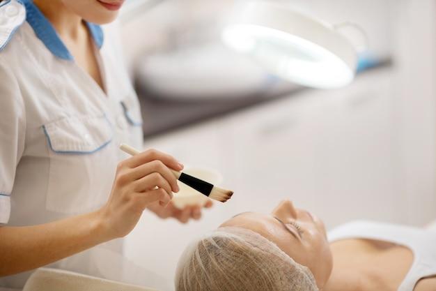 Em uniforme branco. dermatologista de uniforme branco segurando escova com máscara facial enquanto trabalha duro