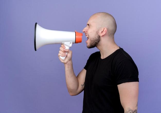 Em vista de perfil, jovem esportista fala no alto-falante isolado no roxo