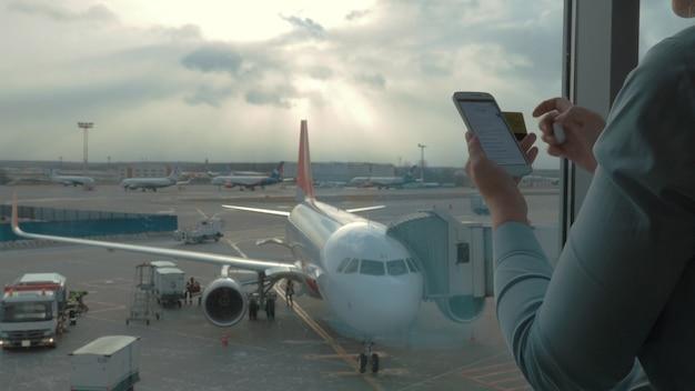 Em vista do aeroporto de mulher fazendo pagamento com cartão bancário usando smartphone e dongle para digitalizar o cartão do banco contra o avião e a pista. aeroporto internacional domodedovo, moscou, rússia