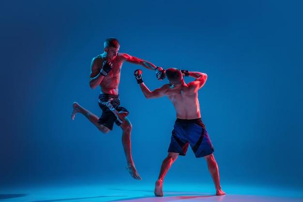 Em vôo. mma. dois lutadores profissionais socando ou boxe isolado no fundo azul do estúdio em néon. fit atletas caucasianos musculosos ou lutadores de boxe lutando. esporte, competição e emoções humanas, anúncio.