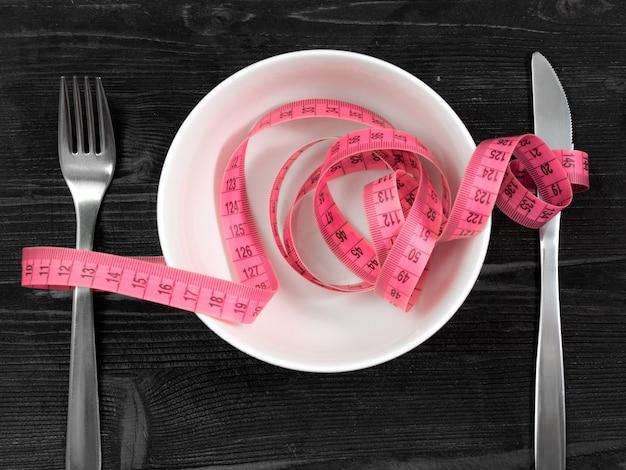 Emagrecimento conceito de dieta de saúde e perda de peso - faca tigela e talheres de garfo e fita métrica curva