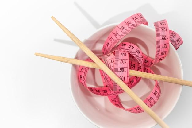 Emagrecimento, dieta saudável e conceito de perda de peso - pauzinhos de tigela, palitos de comida e fita métrica curva