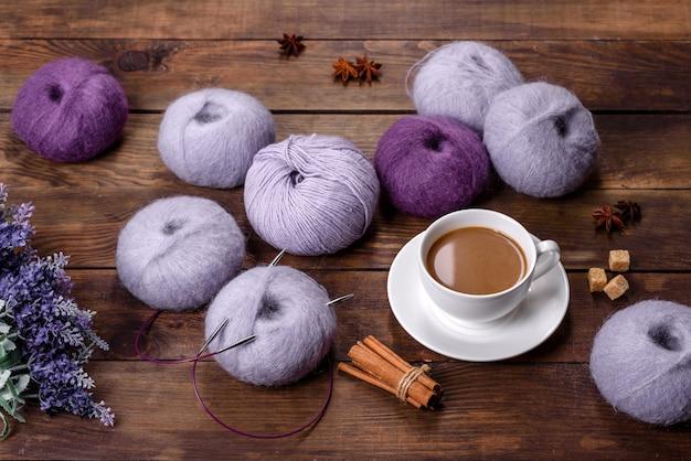 Emaranhados de fios de lã e raios com uma xícara de café e açúcar em uma mesa de madeira. trabalho manual, hobby