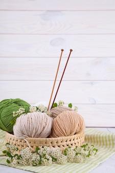 Emaranhados multicoloridos de fios em uma cesta de vime em cima da mesa. estilo japonês wabi sabi. conforto em casa, artesanato.