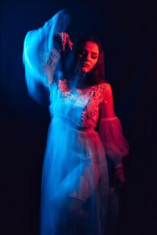 Embaçada mulher em um vestido está dançando em um fundo escuro