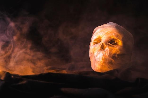 Embalado em saco de plástico crânio iluminado pela luz laranja