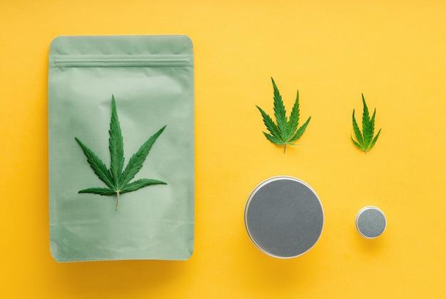 Embalagem artesanal verde com folha de cannabis e potes de metal. diferentes tamanhos de pacotes de cannabis, legalização do comércio de ervas daninhas. farmácia drogas maconha medicinal em fundo amarelo.