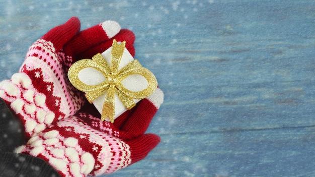 Embalagem da caixa de presente da cor do ouro nas mãos de uma menina