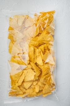 Embalagem de aperitivo de milho mexicano tradicional triangular de nachos, em mesa branca, vista de cima ou lay-out