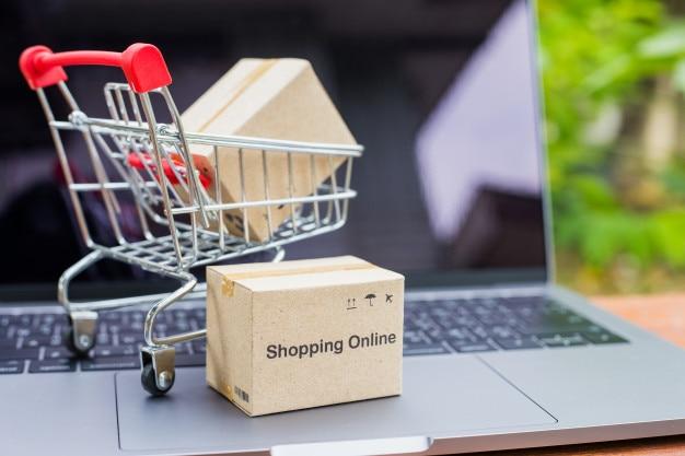 Embalagem de caixas de logística e carrinho de saco de compras no laptop