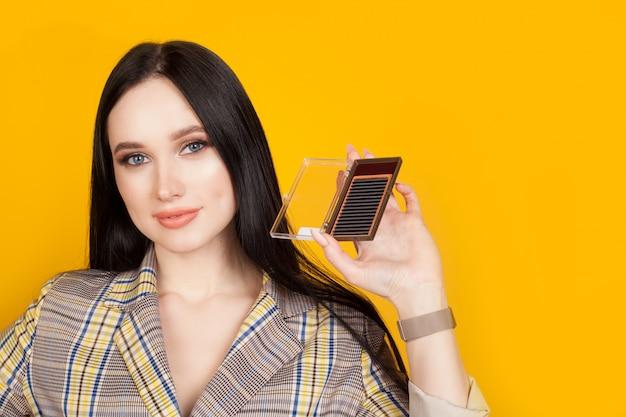 Embalagem de cílios artificiais nas mãos de um mestre de extensão de cílios, em uma parede amarela. o conceito de extensões de cílios, publicidade de material para salões de beleza.