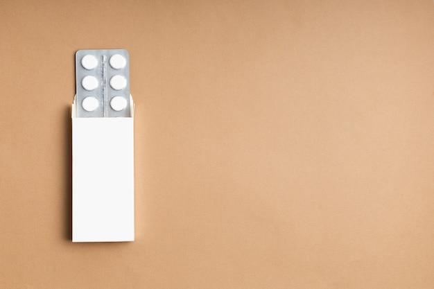 Embalagem de comprimidos brancos em fundo colorido