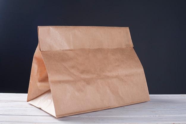 Embalagem de papel artesanal na mesa de madeira branca e fundo escuro. copie o espaço