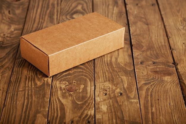 Embalagem de papelão artesanal sem etiqueta apresentada em mesa de madeira escovada estressada, closeup