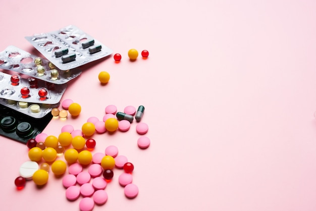 Embalagem de pílula medicamentos multicoloridos saúde farmacêutica fundo rosa