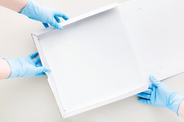 Embalagem de pizza em caixa de papelão vazia e mãos em luvas cirúrgicas médicas para quarentena