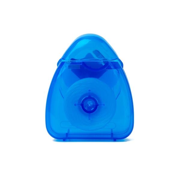 Embalagem de plástico azul com fio dental isolado no fundo branco, close-up