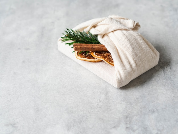 Embalagem de presente reutilizável de tecido ecológico com brunch de abeto, pau de canela e fatia de laranja seca. alternativa sustentável reutilizável para embrulho de presente de natal. zero conceito de desperdício.
