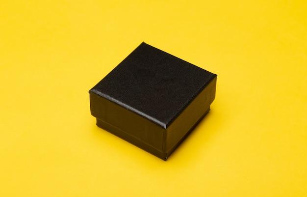 Embalagem de produto mini caixa preta isolada na parede amarela