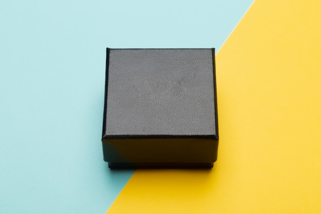 Embalagem do produto mini caixa preta isolada em amarelo azul meio