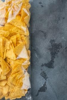 Embalagem transparente de nachos triangulares tradicionais de milho, em mesa cinza, vista de cima ou lay-out