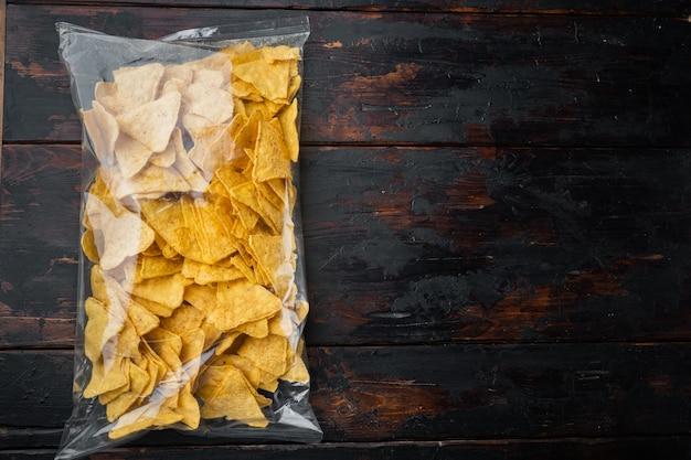 Embalagem transparente de nachos triangulares tradicionais de milho, em mesa de madeira velha, vista de cima ou lay-out