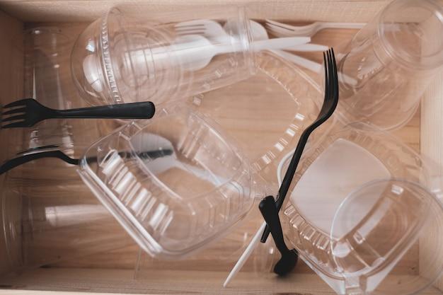 Embalagens plásticas de alimentos na caixa de madeira para reciclagem e preocupação com o aquecimento global ambiental.