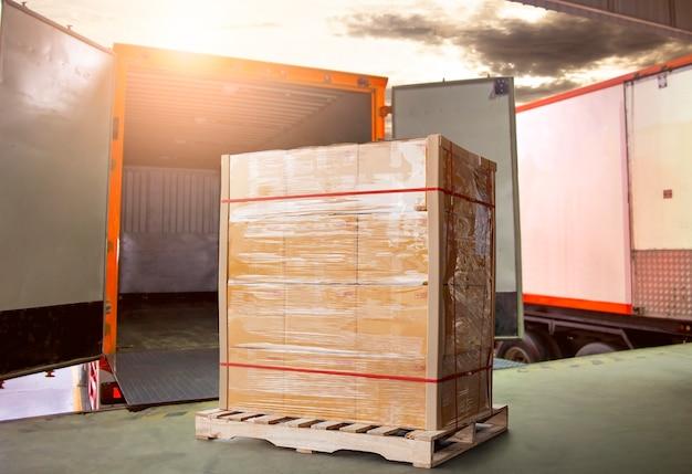 Embalar caixas carregar com caminhões contêineres de carga carregamento estacionado no armazém de cais transporte logístico
