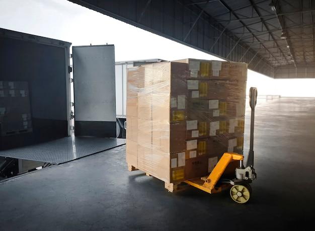 Embalar caixas carregar com caminhões contêineres de carga carregamento estacionado no armazém de doca transporte logístico