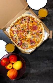 Embale a caixa com pizza, maçãs e pratos em uma mesa