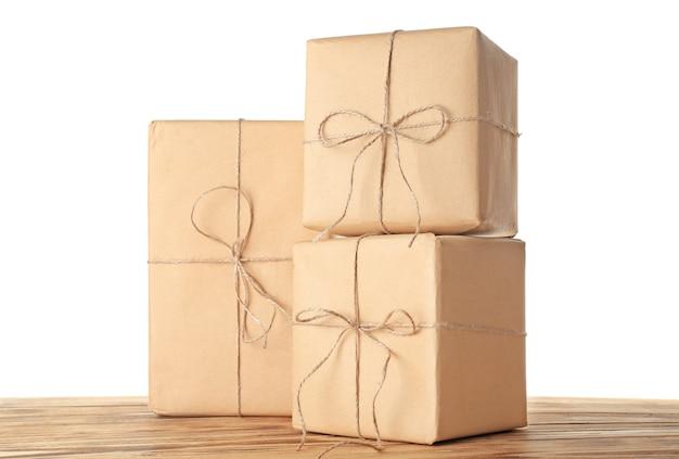 Embale caixas de presente na mesa de madeira contra um fundo branco