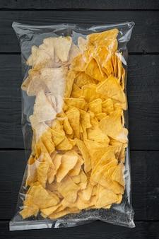 Embale saco de nachos de milho tradicional, em mesa de madeira preta, vista de cima ou plano