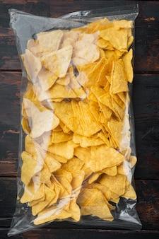 Embale saco de nachos de milho tradicional, em mesa de madeira velha, vista de cima ou plano
