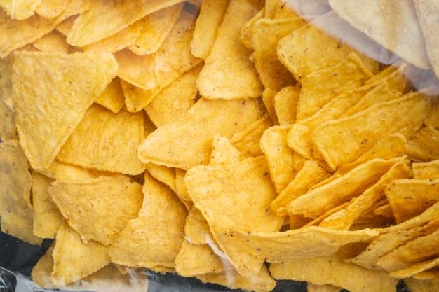 Embale saco de nachos de milho tradicional, em mesa preta, vista de cima ou plano