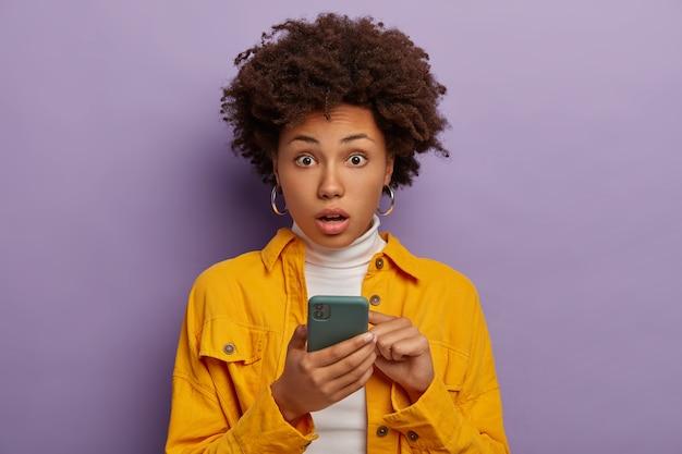 Embaraçada e surpresa, modelo feminina de pele escura levanta as sobrancelhas do choque, segura um celular moderno, usa brincos e jaqueta amarela.