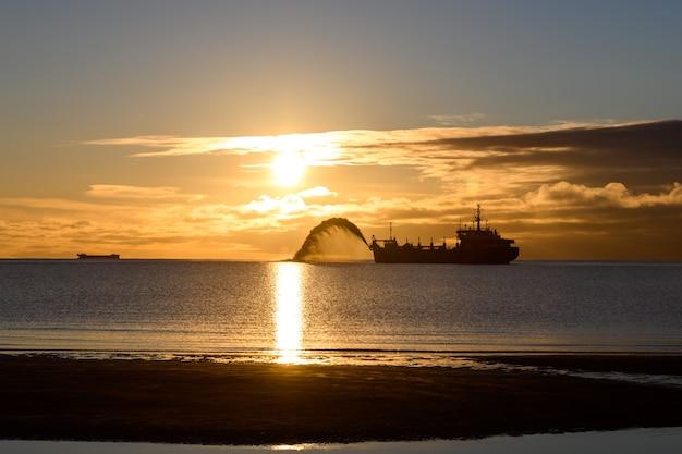 Embarcação empenhada na dragagem na hora do pôr do sol