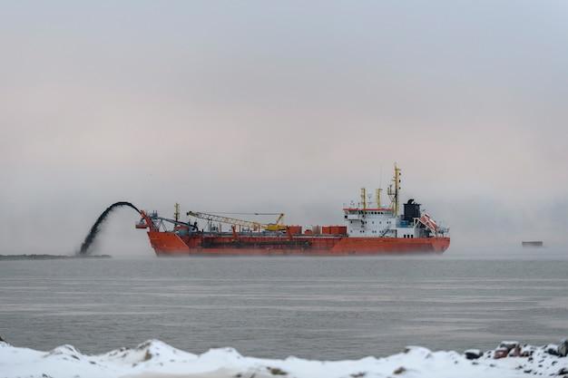 Embarcação envolvida na dragagem na hora do pôr do sol. draga de funil trabalhando no mar. envie o material de escavação de um ambiente aquático.