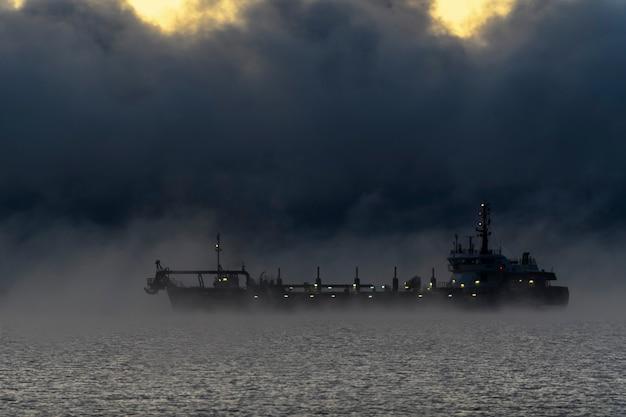 Embarcação restrita em sua capacidade de manobra em movimento usando o motor durante a noite. embarcação envolvida em dragagem. draga trabalhando no mar. regulamentos de colisão.