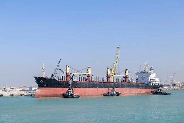 Embarcação se aproximando para atracar com auxílio de rebocadores. operações de amarração. bulker. navio de carga seca.